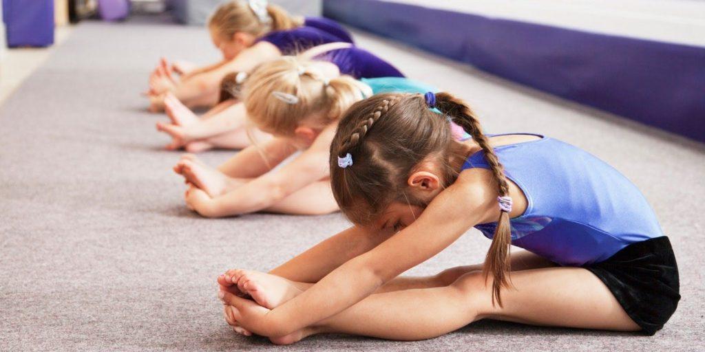 Дети дошкольного возраста выполняют упражнение на растяжку