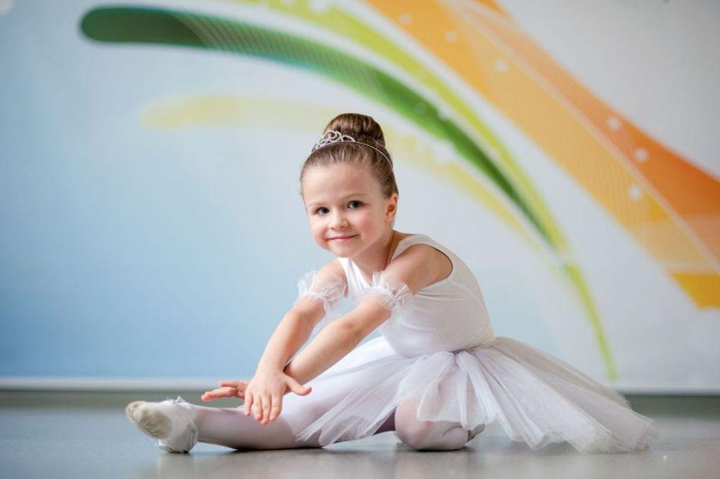 Девочка в белом костюме перед танцевальным выступлением