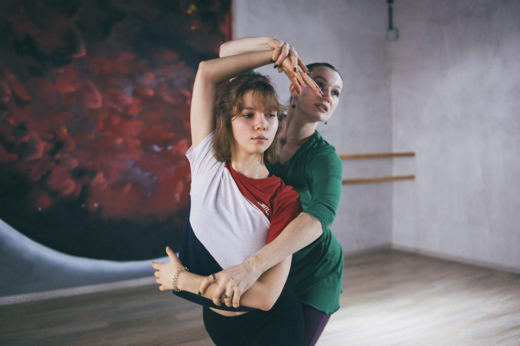 Педагог помогает правильно выполнить движение в боди балете
