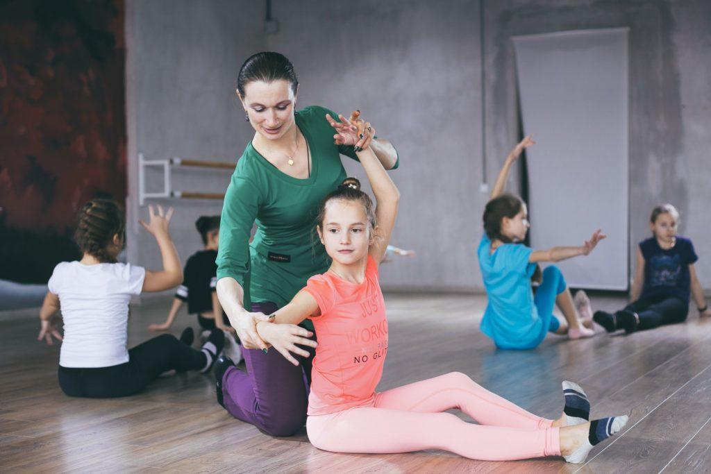 Педагог помогает ребенку освоить танцевальное движение